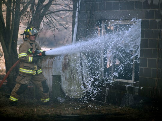 A firefighter shoots water through a busted window, working to contain a workshop that was taken by fire on Monday, February 6, 2017. Thirteen fire companies from Adams County and Maryland respond.