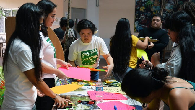 University of Guam students and members of Prutehi Litekyan: Save Ritidian prepare posters for a march around the Mangilao campus on Sept. 25, 2017.