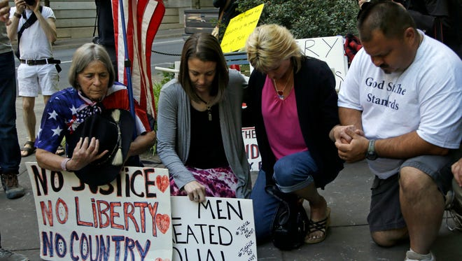 Protesters kneel in prayer outside the federal courthouse in Portland, Ore., on Sept. 13, 2016.