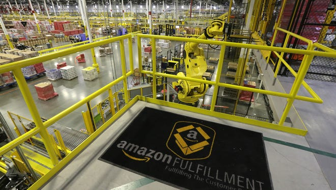A giant yellow robotic arm is shown working at right, Nov. 30, at Amazon.com's fulfillment center in DuPont, Wash.