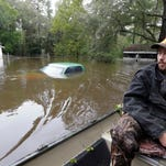 A vehicle and a home are swamped with floodwater from nearby Black Creek in Florence, S.C., Monday, Oct. 5, 2015. Flooding continues throughout the state following record rainfall amounts over the last several days. (AP Photo/Gerry Broome)