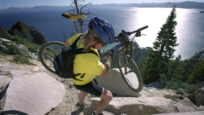 Back country mountain bike patroller Dale Roberts carries his bike across a rock slide along the Flume trail above Lake Tahoe in 2002.