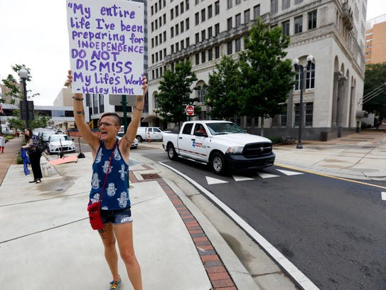 Amelie Hahn of Jackson, waves a message sign Thursday