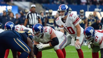 Quarterback Eli Manning (10) of the New York Giants  prepares for the snap during the fourth quarter of the game between the Los Angeles Rams and the New York Giants  at Twickenham Stadium.