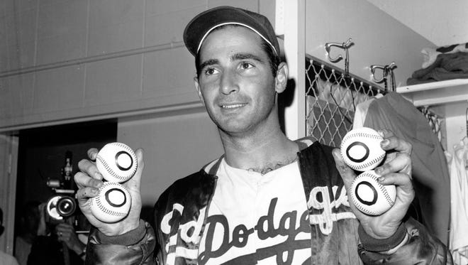 Sandy Koufax, after his perfect game on Sept. 9, 1965, poses with baseballs representing each of his four no-hitters.