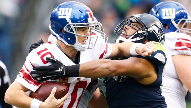Giants quarterback Eli Manning, left, is pressured by Seattle's Jordan Hill during the second quarter at CenturyLink Field on Sunday.