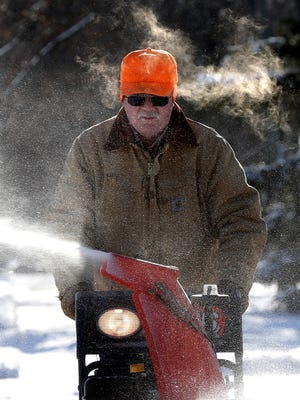 Wayne Hatton clears snow from his sidewalk in sub-zero temperatures on January 5, 2015 in Little Chute, WI.