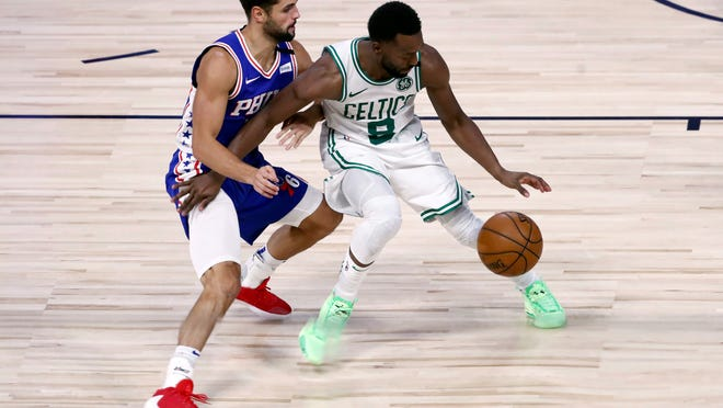 Boston Celtics guard Kemba Walker (8) dribbles as Philadelphia 76ers guard Raul Neto (19) defends during the second half of Game 4 of an NBA basketball first-round playoff series, Sunday, Aug. 23, 2020, in Lake Buena Vista, Fla.