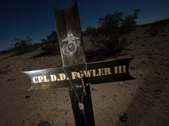 A wooden cross stands in the desert east of Twentynine Palms, marking the spot where Marine Cpl. Donald D. Fowler III was killed in a car accident. Fowler, an Iraq war veteran, lost control of his yellow Mustang while speeding down Highway 62 on Feb. 7, 2011.