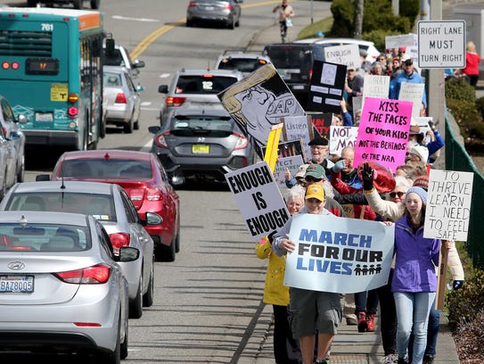 "The ""March For Our Lives "" protest around the Kitsap Mall in Silverdale Saturday was lead by Liam Junten, 14, from Port Orchard (middle) and Kate Zabinski, 14, from Silverdale ."