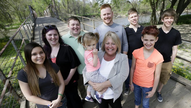 In this Tuesday, April 26, 2016 photo, Denise Moore, center, in white, of Des Moines, Iowa, poses with her family, from left, daughter Alex Gibbs, Emily Bosch, son Kodi Baughman, granddaughter MacKenzie Moore, sons Kori Moore, Kelli Moore, daughter Andy Gibbs, and son Kasi Baughman during a visit to Water Works Park, in Des Moines, Iowa. Moore, a mother of seven, nearly lost her parental rights after her arrest in 2003 for conspiracy to deliver methamphetamine.