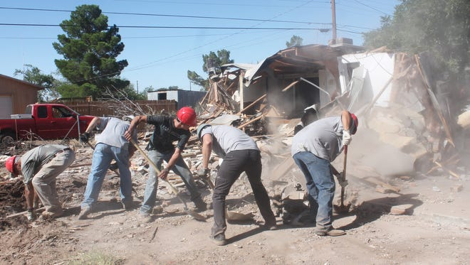 Airmen from Holloman Air Force Base work shoveling debris during the demolition of a Tularosa home. This home will now be replaced with a brand new manufactured home under a White Sands Habitat for Humanity program.
