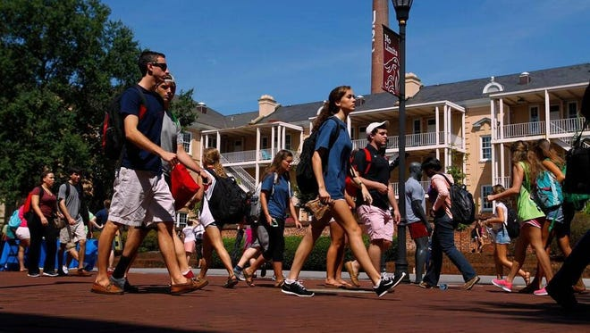 University of South Carolina students make their way past the Russell House on campus.