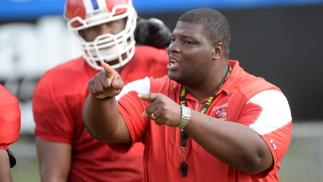 Evangel head coach Byron Dawson works with his defensive line during a recent team practice.