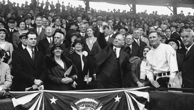 President Herbert Hoover throws out the ceremonial first pitch in Washington on April 14, 1931, before a game between the Senators and the world champion Philadelphia Athletics.