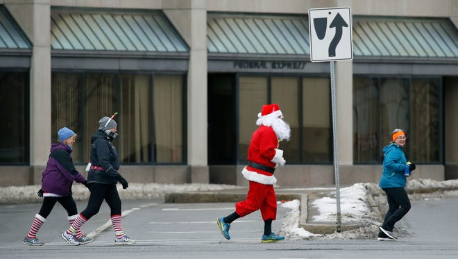 Christopher Herman (aka Santa) participates in the third annual Christmas Day Charity Run to benefit House of Mercy.
