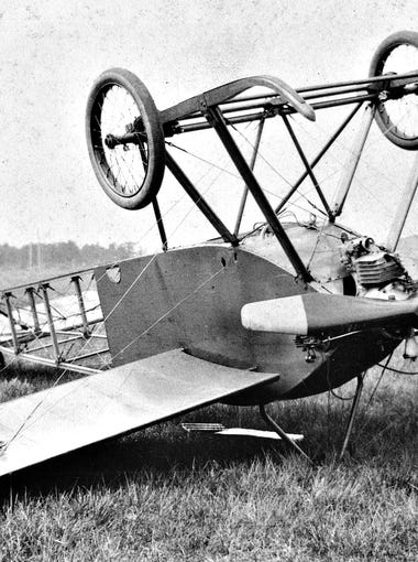 An airplane flipped on its back, circa 1910s.