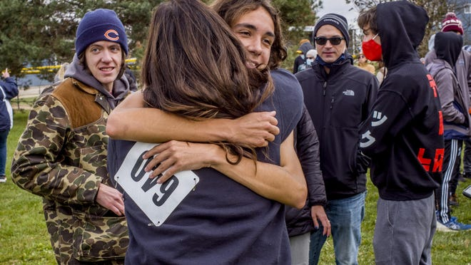 Olympia Spartan Charlie Kistner takes in a round of hugs Saturday, October 24, 2020 after his first place finish in the Class 1A Boys Cross Country Regionals at Olympia High School in Stanford.