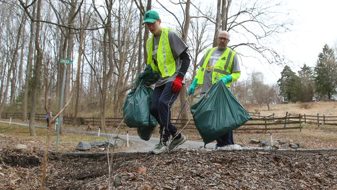 Newark Charter School student Ryan Lynch (left) and his father, Tom, scout for trash along Del. 82 as part of the Red Clay Valley Clean Up headed by the Brandywine Red Clay Alliance Saturday morning.
