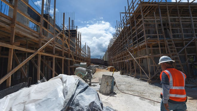 A BME & Sons, Inc. construction worker walks through the Alegria Townhouse Project building site in Tumon on March 14, 2017. Company owner Bernie Maranan said he is losing about 60 percent of his workers at the end of this month because of visa restrictions, and it is unclear when the project can be completed.