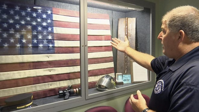 In this Aug. 22, 2016, image taken from video, EMS Coordinator Jim Etzin motions toward a glass case at the Farmington Hills Fire Department in Farmington Hills, Mich. The case contains items that commemorate the efforts of first responders during the Sept. 11, 2001, terror attacks. Etzin, then a Farmington Hills firefighter/paramedic, and eight other members of southeastern Michigan's firefighting community took part in a 755-mile walk from the Ambassador Bridge in Detroit to the Brooklyn Bridge a month after the attacks. (AP Photo/Mike Householder)