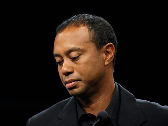 FILE - In this March 24, 2014 file photo, Tiger Woods looks down during a news conference at the Newseum in Washington. Woods says his recovery from back surgery is going slowly and he's not sure when he'll be able to return to golf. In a wide-ranging blog on his website Monday, May 5, 2014, Woods says he remains sore from the incision during the March 31 operation for a pinched nerve. (AP Photo/Susan Walsh, File)