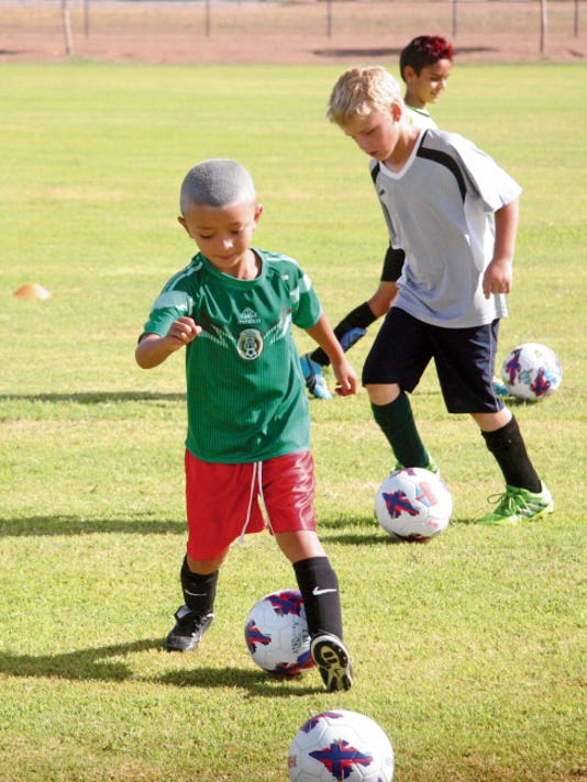 Matt Hollinshead — Current-Argus Alex Cortez, 6, tries to move a soccer ball with his heel (one of the dribbling techniques learned) during the Challenger Soccer Camp Friday, July 18, 2014 at Bob Forrest Youth Sports Complex. The camp will be held in Carlsbad again this year on July 13-17.