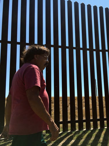 Jose Manuel Reyes walks along the border fence that is located in his backyard on Wednesday, May 25, 2017, at his home in Brownsville.