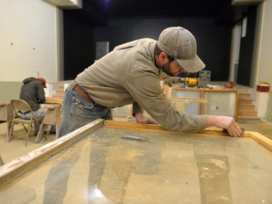 John Larson of Urick Log Homes refinishes windows for