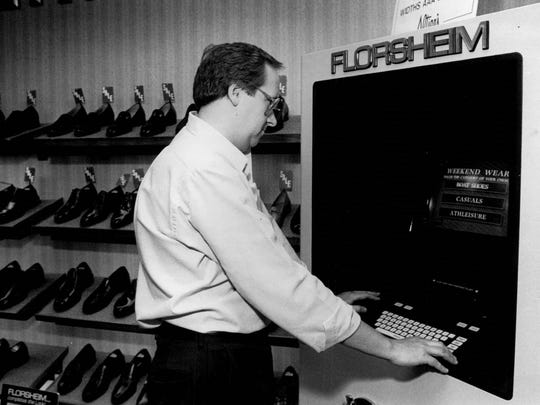 Gary Clark takes time during his lunch hour to look through the selection of shoes displayed in the then-new shoe machine at Altier's in Midtown Plaza.