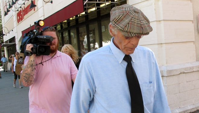 Thomas George Paculis walks past reporters after pleading guilty in federal court to attempting to extort $200,000 from celebrity cook Paula Deen.