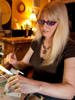 Local glassworker Robin Holt creates a focal bead in her home workshop in Tallahassee.