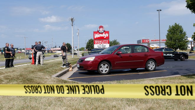 Nixa police investigate the scene where a dead body was found in the back seat of a maroon Chevrolet Malibu in the Wendy's parking lot at 441 W Aldersgate Drive on Thursday, June 23, 2016.