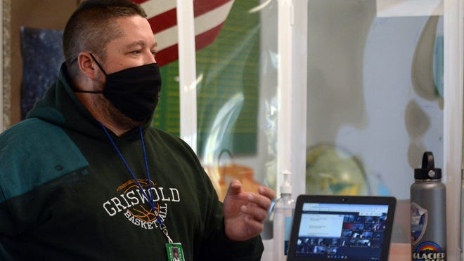 John Felty, a Griswold Middle School social studies teacher, talks masked and near a partition to students physically in his class and remote students Thursday. See video at NorwichBulletin.com