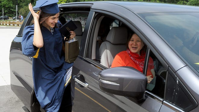Leilani Schulting, of Belmont, gets back into the car after receiving her drive-up diploma at Minuteman High School Commencement Ceremonies held Friday.