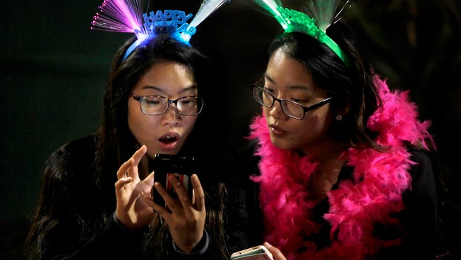Indiana visitors Ivy and Jessica Yen check out their phones during the New Year's Eve Downtown Countdown celebration Wednesday.
