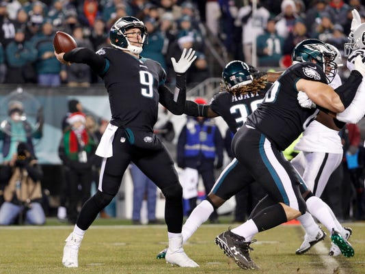 FILE - In this Dec. 25, 2017, file photo, Philadelphia Eagles' Nick Foles throws a pass during the first half of the team's NFL football game against the Oakland Raiders in Philadelphia. The Eagles have already lost several important players to injury, including MVP candidate Carson Wentz. They can't afford to lose backup quarterback Foles. But the offense struggled in the last game and Foles could use the reps with his receivers. Coach Doug Pederson is weighing the importance of protecting players from injury and keeping them sharp, as the team prepares to play the Dallas Cowboys this week. (AP Photo/Chris Szagola, File)