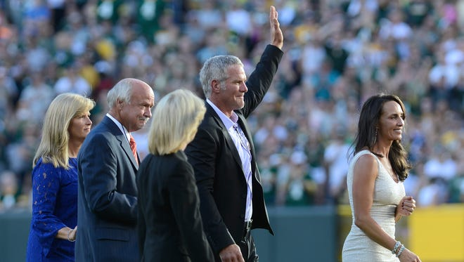 Brett Favre waves to the fans as he makes his way to the tunnel after the ceremony honoring him at Lambeau Field in Green Bay, Wis. on Saturday, July 18, 2015.