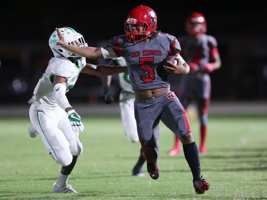North Fort Myers High School's Fa'najae Gotay eludes Fort Myers defenders during first quarter play Friday at North Fort Myers High School. North beat Fort Myers 34-17.
