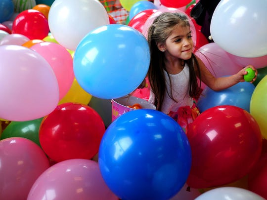 Leila Esquibel, 3, makes her way through the balloons to find eggs following Easter service Sunday, April 5, at Connection Life Church in Salem.