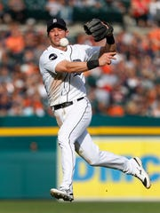 Tigers second baseman Andrew Romine throws to first