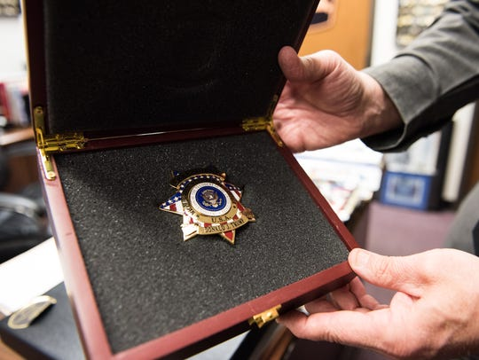 Wicomico County Sheriff Mike Lewis holds a commemorative