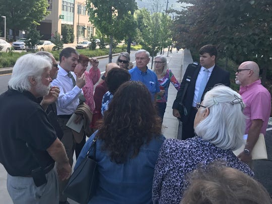 Attorney John D. Noor of Asheville-based Roberts & Stevens meets with East Asheville residents July 31, 2018 outside the Buncombe County Courthouse. Noor was hired to represent the neighborhood by Timothy and Jennifer Heim and Timothy Burleson.