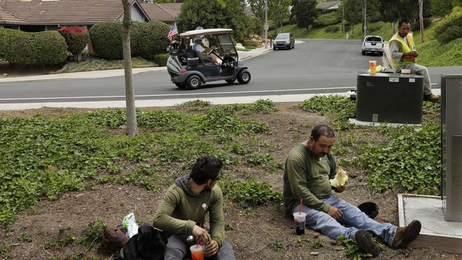Duncan Wallace drives a golf cart from his house to his golf club as landscape workers take a break in Vista, Calif., in May. Income inequality has surged near levels last seen before the Great Depression.