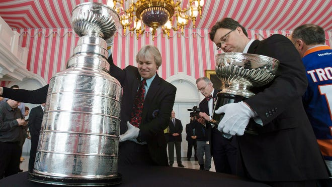 Phil Pritchard, left, picks up the Stanley Cup as Craig Campbell, right, holds the original Stanley Cup following an event commemorating the Cup's 125th anniversary at Rideau Hall Thursday March 16, 2017 in Ottawa. *Adrian Wyld/The Canadian Press via AP)