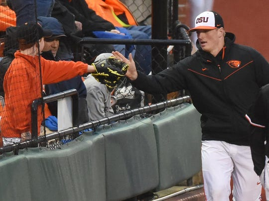 Oregon State's Drew Rasmussen reaches out to greet a young fan during a game against San Jose State on March 24, 2015, at Goss Stadium. Rasmussen tossed the first perfect game in school history on March 21 against Washington State.