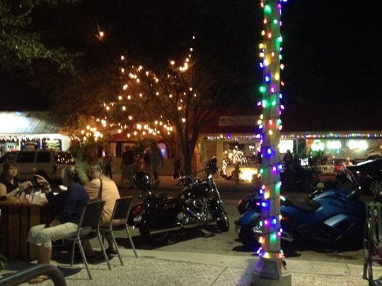 Holiday lights create a festive atmosphere at the Taste of Jensen. Patrons can sample food and beverages from 23 Jensen Beach restaurants as well as shop for arts and crafts at a Christmas marketplace.
