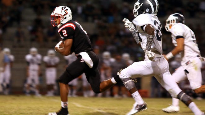 Palm Springs' Tayler Hawkins breaks away from the Redlands defense for a touchdown during the first half of the game in Palm Springs on Friday night, September 4, 2015.