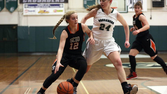 Scio sophomore McKenzie Reger (12) dribbles past Salem Academy sophomore Sydney Brown (24) at a game at Salem Academy on Wednesday, Feb. 17, 2016. Salem Academy won the game 34-23.