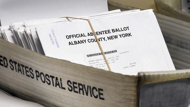In this June 30, 2020, file photo, a box of absentee ballots wait to be counted at the Albany County Board of Elections in Albany. New York will allow voters to request absentee ballots for the general election because of coronavirus under a new state law signed Thursday, Aug. 20. Lawmakers passed the bill last month, and voting rights groups have been calling on Gov. Andrew Cuomo to sign the legislation for weeks.
